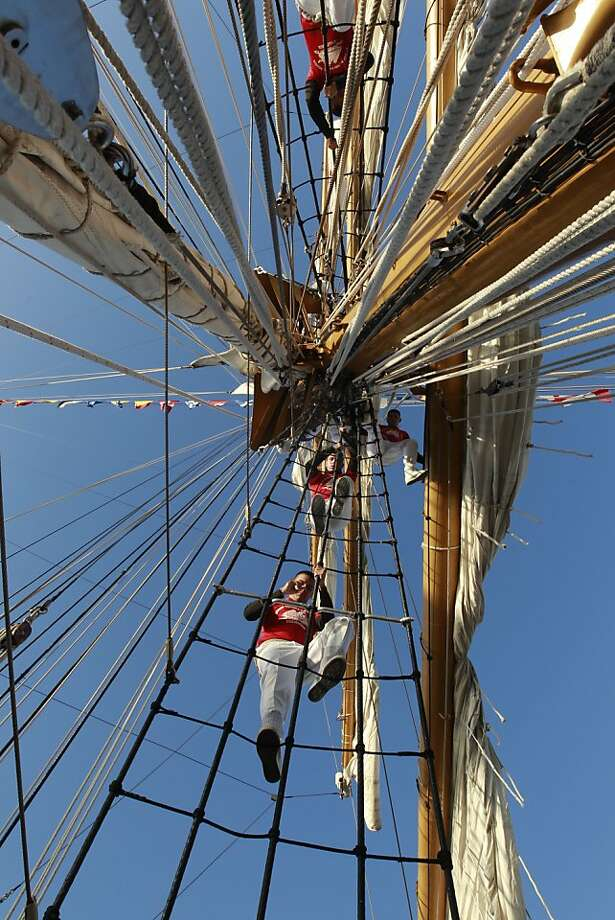 """Riggers climb down from their positions on the yards above as the """"Gloria"""" a Colombian navy sailing ship on Friday Oct. 25, 2013, pulls into port at pier 17 along the Embarcadero in San Francisco, Calif. Photo: Michael Macor, The Chronicle"""