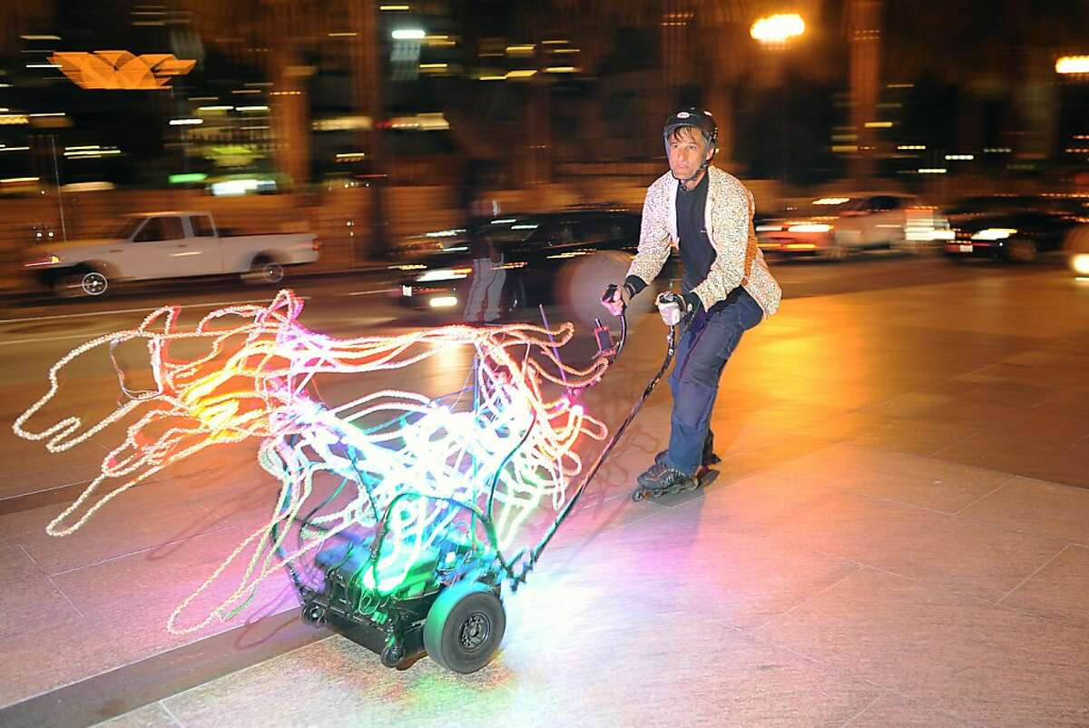 Kenny Forrest skates around with his motorized LED light dog sculpture before the start of the Friday Night Skate event in San Francisco, California Friday, August 9, 2013.