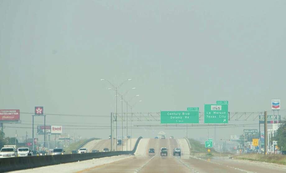 Smoke drifts over the I-45 near Texas City, Friday, Oct. 25, 2013. Photo: Cody Duty, Houston Chronicle / © 2013 Houston Chronicle