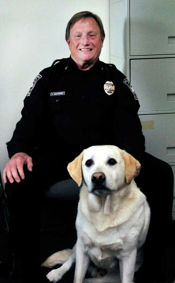 Brookfield Police Chief Robin Montgomery sits with Guinness, his dog, in the Brookfield, Conn., police station Friday, Oct. 25, 2013. Photo: Michael Duffy / The News-Times