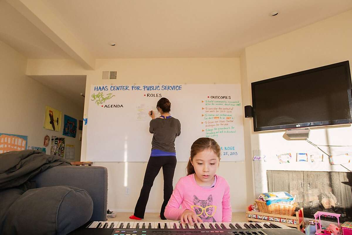Giselle Chow at home prepares a board for a Hass Center for Public Service staff retreat she will be facilitating, while her daughter Malia practices the keyboard, before Giselle takes her kids to school, San Francisco, CA, September 23rd, 2013.