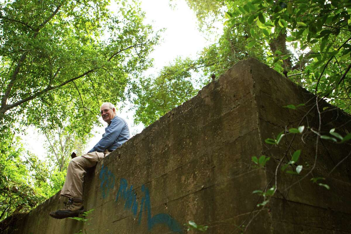 Louis Aulbach, Vicepresident of Houston Archeological Society sits on the ruins of what it used to be a wood bridge part of the military training area Camp Logan. The camp was closed in 1919. The Houston Archeological Society is working with the local government to make studies on the site. Monday, Oct. 21, 2013, in Houston. ( Marie D. De Jeséºs / Houston Chronicle )
