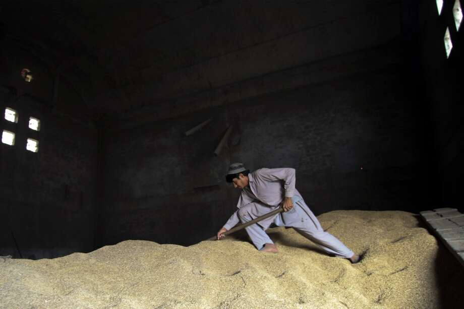 Pakistan: A worker rakes rice grain at the Amin Ittefaq Rice Mills rice-processing factory in Bucheki village in the district of Faisalabad in Punjab, Pakistan. Prime Minister Nawaz Sharif's four-month-old government is struggling to revive the $231 billion economy crippled by chronic energy shortages and a spike in violence from a Taliban insurgency in the northwest. Photo: Asad Zaidi, Bloomberg