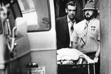 One of thirteen people found dead February 18, 1983 in a private club in  Seattle's International District is removed from the scene of the crime.