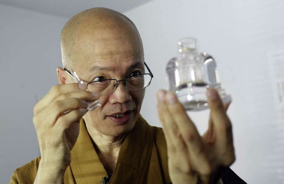 Dharma Master YongHua displays a bottle containing aromatic shariras, part of his temple's collection of Buddhist relics. Photo: Damian Dovarganes / Associated Press