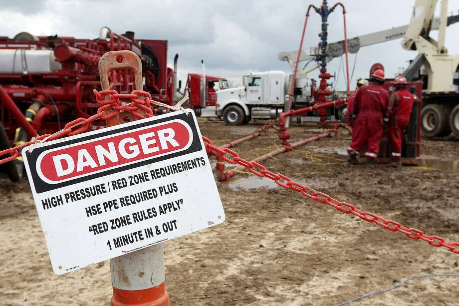 Red-zone warnings are posted  at  a well  near the Jim Wells-Duvall county line. Wells face big drop-offs in output after the first year, normal  in shale drilling. To offset declines, more wells are drilled. Photo: Jerry Lara / San Antonio Express-News
