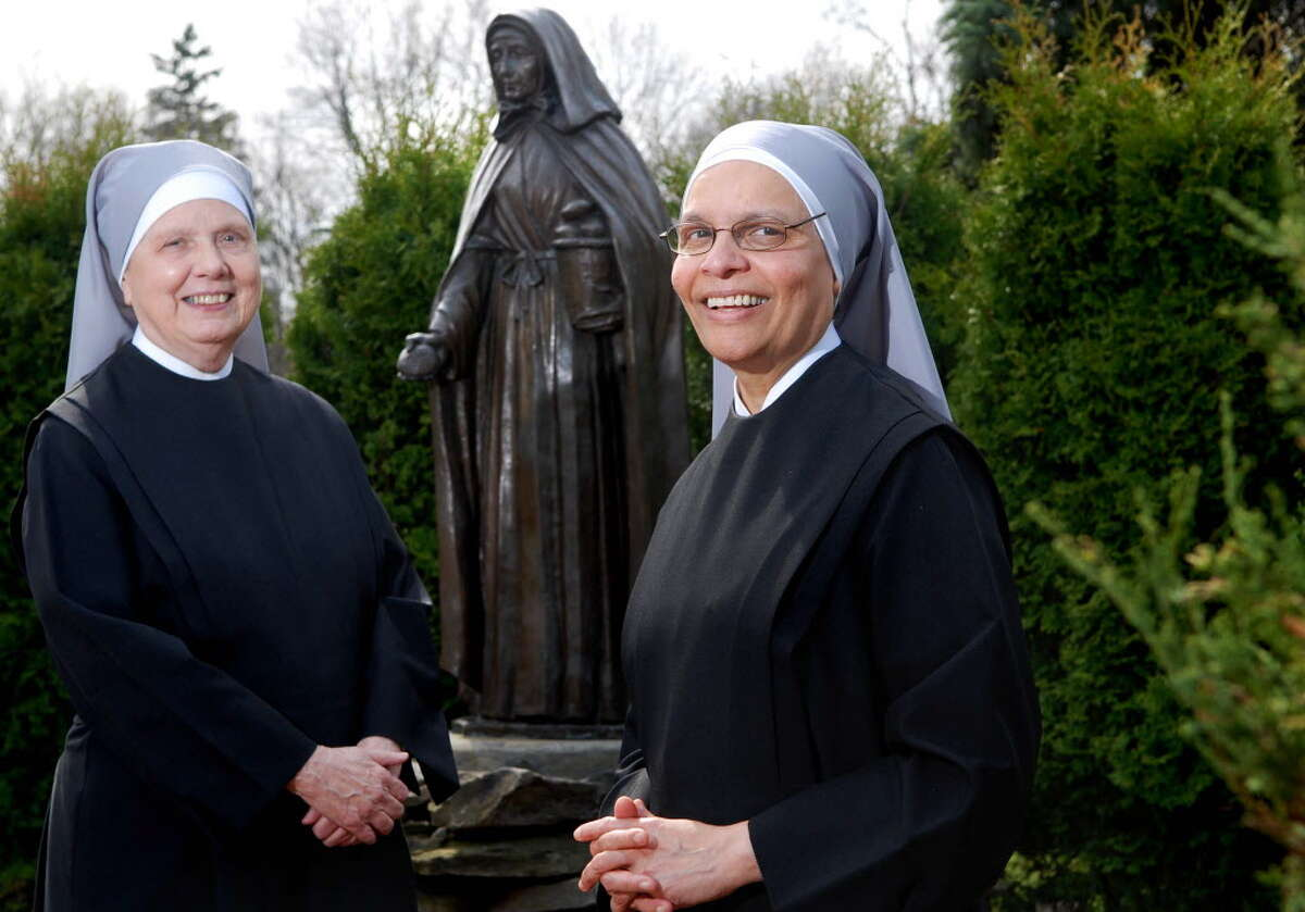 In this 2010 photo, Sister Frances MacKay, left, and Mother Superior Celine Therese of the Little Sisters of the Poor pose for a photo at Our Lady of Hope Residence in Latham, NY. Behind them is the statue of Saint Jeanne Jugan, the foundress of the order. (Paul Buckowski / Times Union archive)