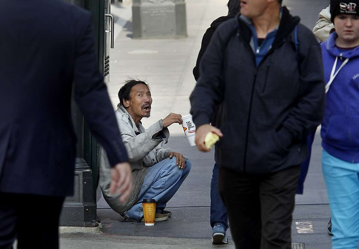 An unidentified panhandler shook a plastic cup to get the attention of pedestrians Tuesday October 22, 2013 in San Francisco, Calif. The Union Square Business Improvement district surveyed 150 panhandlers in the area, getting a wealth of information about who's begging and who's giving.