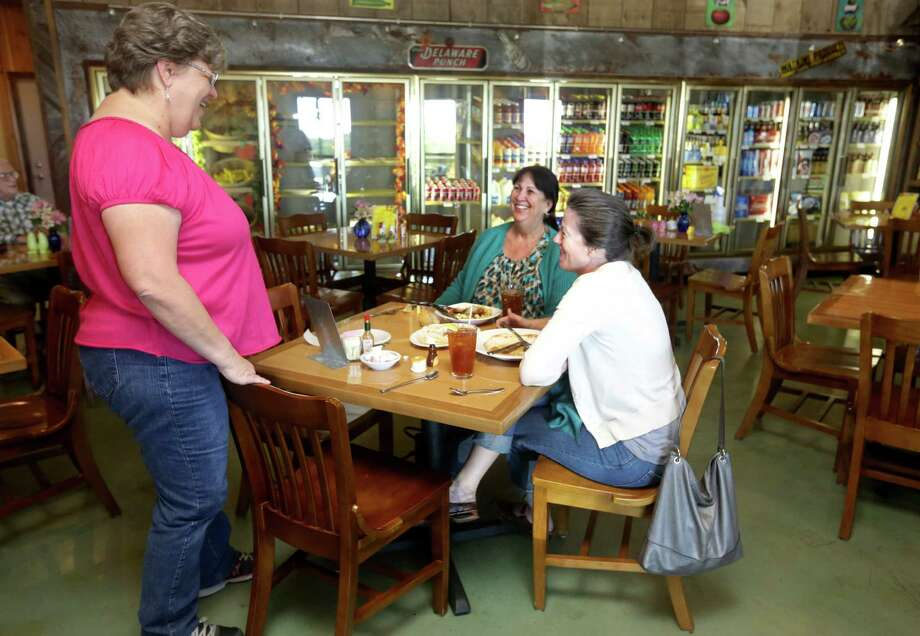 Royanne Smith, left, manager of Cafe at the Ridge, chats with customers Jackie Ashley, right, and Denise Jenschke as they enjoy lunch, Thursday, Oct. 24, 2013. The owners of Cafe at the Ridge were instrumental in getting the issue of selling alcoholic beverages, in parts of Gillespie County, on the upcoming ballot. Photo: Bob Owen, San Antonio Express-News / ©2013 San Antonio Express-News