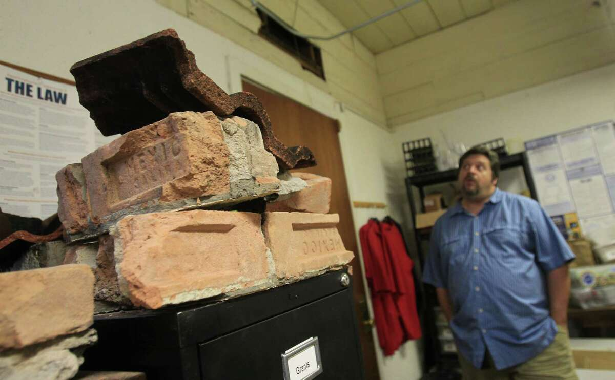 Tristan Smith, Executive Director of the Houston Fire Museum, stands near the burnt bricks from the 4-alarm hotel fire where four firefighters were killed. There is no storage area to house all the artifacts, so they are placed on top of a filing cabinet in the unfinished staff office.