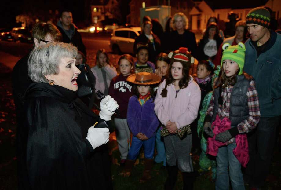 Local author and storyteller Marty Bishop, left, tells a ghost story at the Bethel Haunted Ghost Tour in Bethel, Conn. on Friday, Oct. 25, 2013.  The event, presented by the Bethel Historical Society, toured historic downtown Bethel, making stops to tell ghost stories and the history of ghost sightings in the area. Photo: Tyler Sizemore / The News-Times