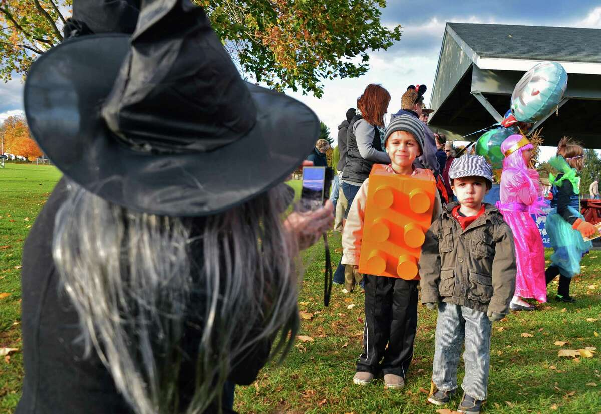 Witchy mom Rita Tomic, left, of Ballston Lake takes a photo of son's, Gregory, 6, who dressed as a Lego block , and Peter, 3, in a train driver costume, Friday Oct. 25, 2013, during the Halloween costume parade at Clifton Common in Clifton Park, N.Y. (John Carl D'Annibale / Times Union)