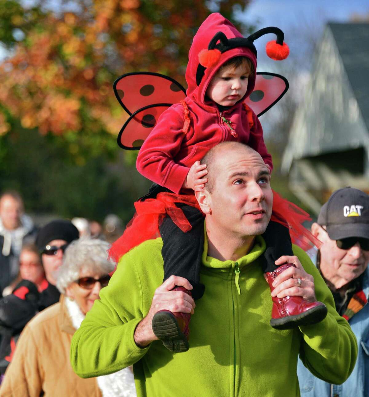 Ladybug Molly Klopfer, 1, rides atop dad's, Scott Klopfer's, shoulders in the Halloween costume parade at Clifton Common Friday, Oct. 25, 2013, in Clifton Park, N.Y. (John Carl D'Annibale / Times Union)