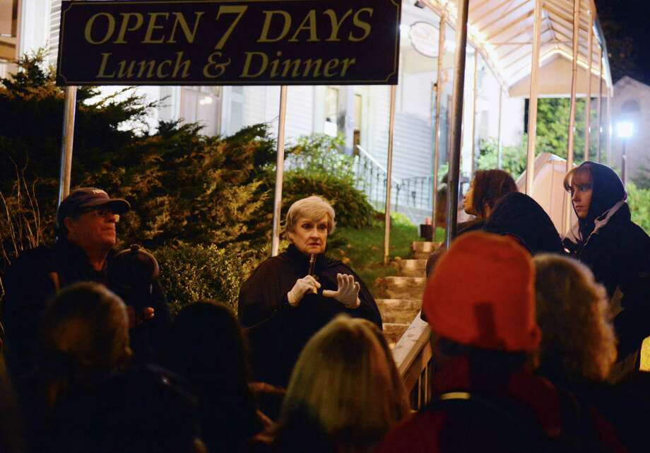 Local author and storyteller Marty Bishop, center, tells stories of ghost sightings at the Putnam House during the Bethel Haunted Ghost Tour in Bethel, Conn. on Friday, Oct. 25, 2013.  The event, presented by the Bethel Historical Society, toured historic downtown Bethel, making stops to tell ghost stories and the history of ghost sightings in the area. Photo: Tyler Sizemore / The News-Times