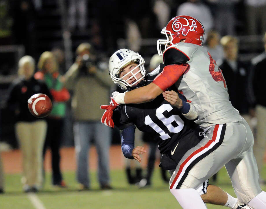 Staples quarterback Jack Massie (# 16), at left, is sacked by Zachary Allen (# 44) of New Canaan causing a first quarter fumble during the high School football game between Staples High School and New Canaan High School at Staples in Westport, Friday night, Oct. 25, 2013. The fumble was recovered by New Canaan and led to a first quarter touchdown. Photo: Bob Luckey / Greenwich Time