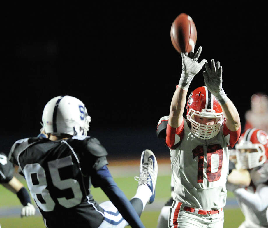 At right, New Canaan's Alexander Dobbin (# 10) deflects the punt of Sean Jensen (# 85) of Staples during the second quarter of the high School football game between Staples High School and New Canaan High School at Staples in Westport, Friday night, Oct. 25, 2013. Photo: Bob Luckey / Greenwich Time