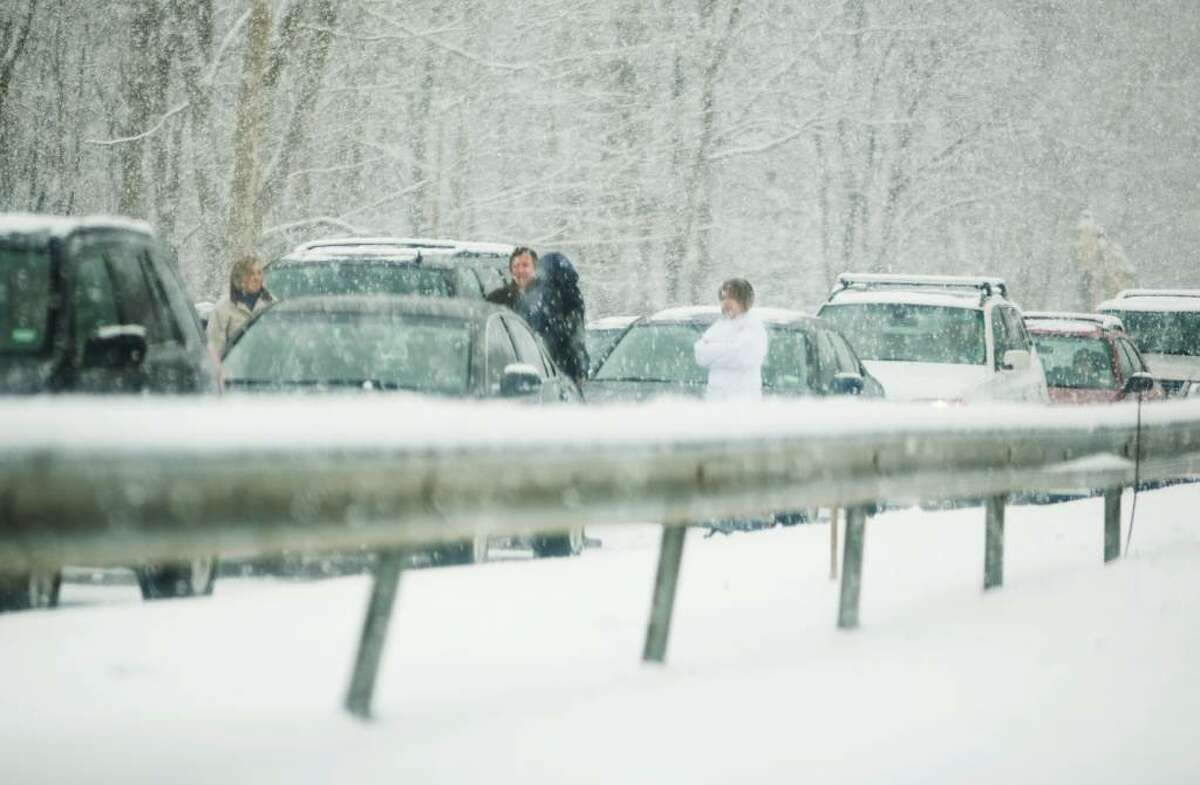 People stand outside their cars on the Merritt Parkway after snow conditions shut down a section in the north-bound lanes in Fairfield near Black Rock Turnpike.
