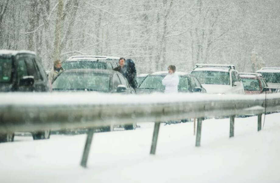 People stand outside their cars on the Merritt Parkway after snow conditions shut down a section in the north-bound lanes in Fairfield near Black Rock Turnpike. Photo: Kerry Sherck / Stamford Advocate