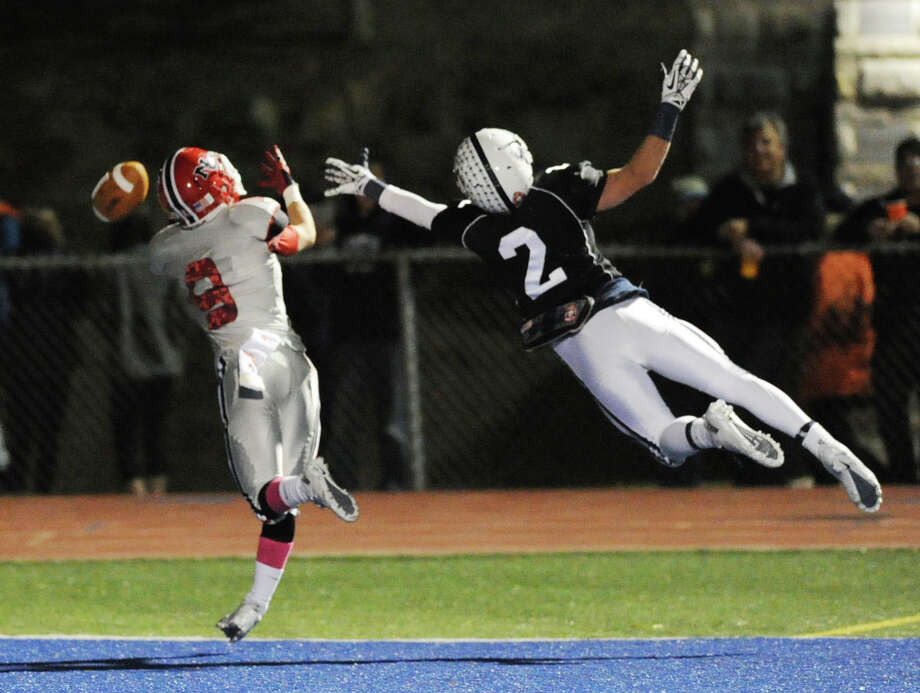 At right, Will Johnson (# 2) of Staples breaks up a pass thrown to Robby Paul (# 8) of New Canaan during the first quarer of the high School football game between Staples High School and New Canaan High School at Staples in Westport, Friday night, Oct. 25, 2013. Photo: Bob Luckey / Greenwich Time