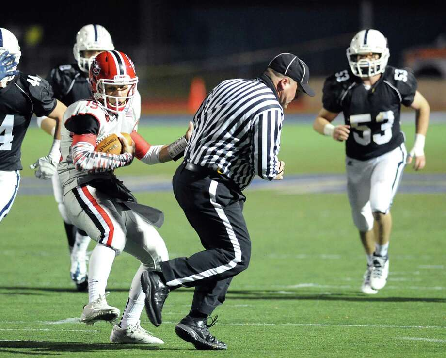 New Canaan quarterback Nick Cascione, at center, runs into a referee during the high School football game between Staples High School and New Canaan High School at Staples in Westport, Friday night, Oct. 25, 2013. Photo: Bob Luckey / Greenwich Time