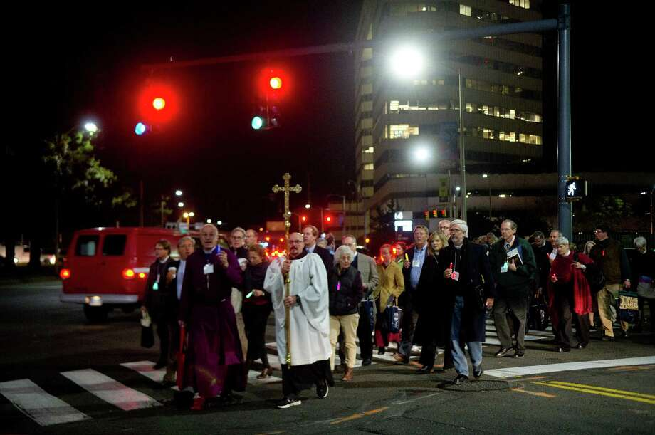 Members of the Episcopal Diocese of Connecticut walk in a processional against violence along Tresser Blvd. to St. John's Episcopal Church in Stamford, Conn., on Friday, October 25, 2013. Photo: Lindsay Perry / Stamford Advocate