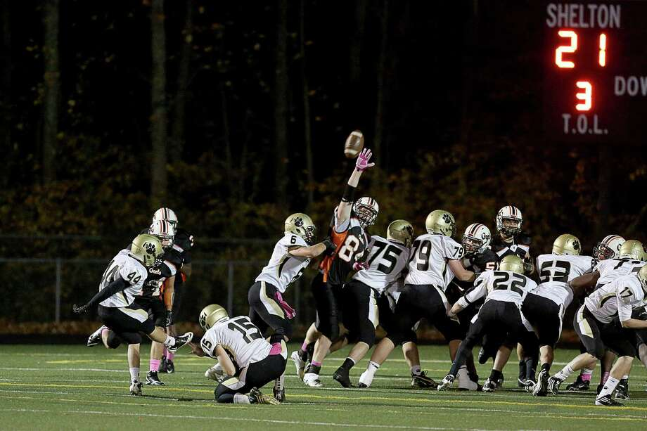 Shelton High School's # 84 Kyle Drost (center) makes an attempt to block extra point on Daniel Hand High School during Friday evening match-up. Photo: Mike Ross / Mike Ross Connecticut Post freelance - @www.mikerossphoto.com