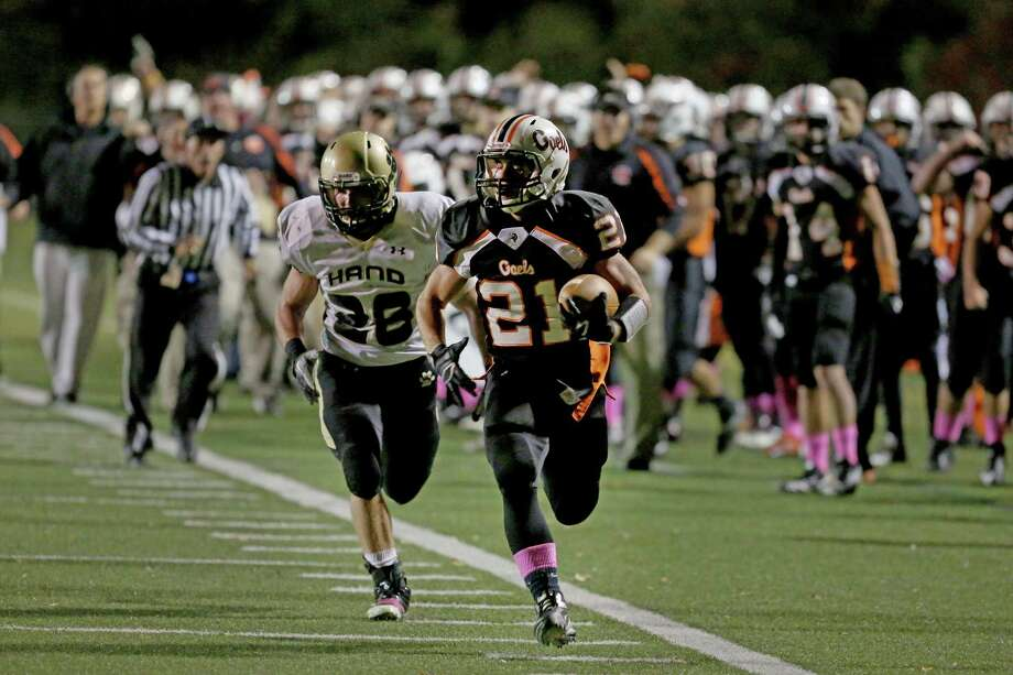 Shelton High School's # 21 Jason Thompson rushes for a long yardage touchdown run as Daniel Hand High School's #26 Taylor Houghton gives chase during Friday evening match-up. Photo: Mike Ross / Mike Ross Connecticut Post freelance - @www.mikerossphoto.com