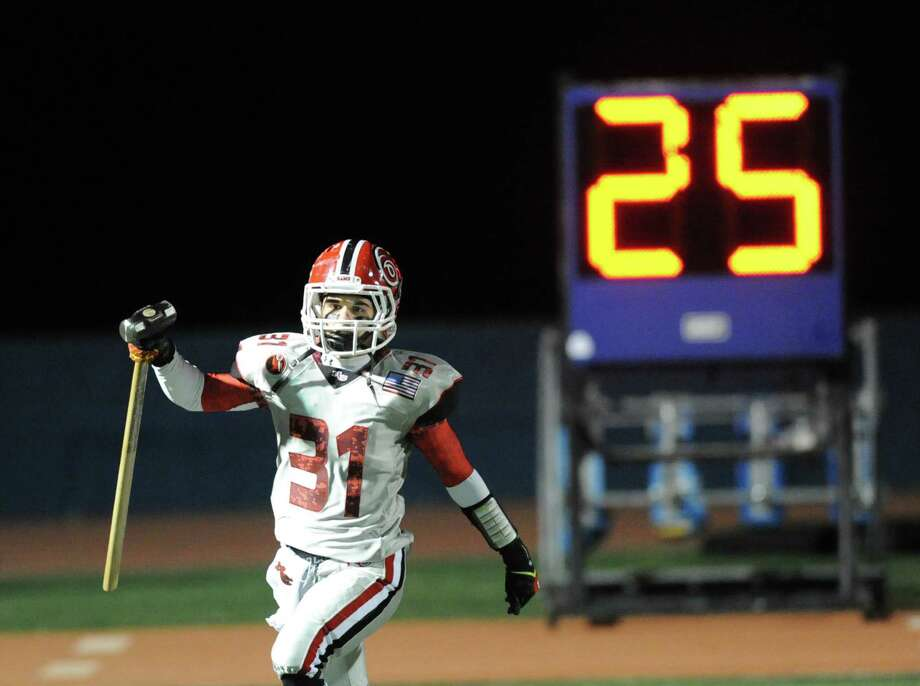 New Canaan's Michael DiCosmo (# 31) carries the sledge-hammer onto the field prior to the start of the high School football game between Staples High School and New Canaan High School at Staples in Westport, Friday night, Oct. 25, 2013. Photo: Bob Luckey / Greenwich Time