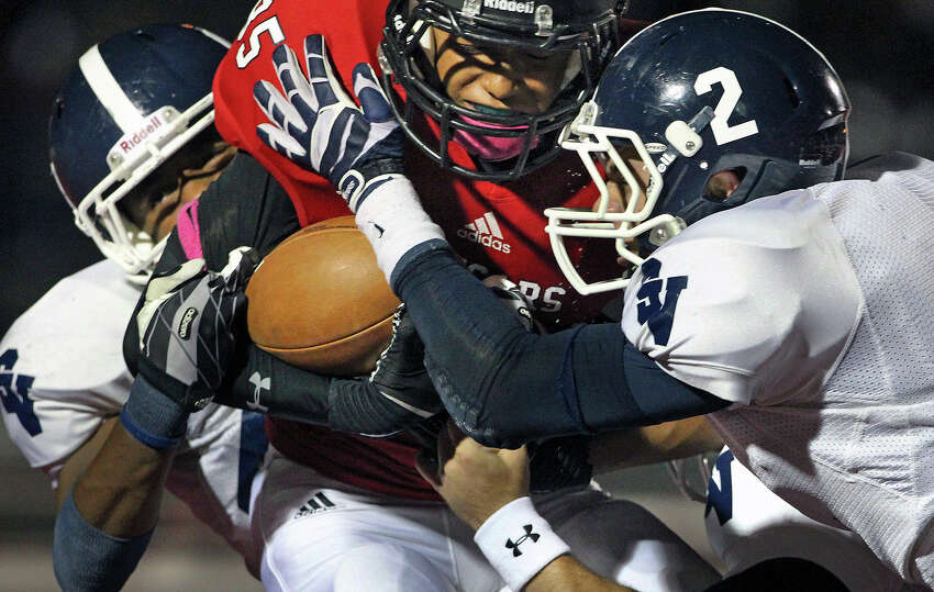 Cougar receiver Trey Scott is smothered by Ranger defender Shane Piatnik and teammates as Canyon hosts Smithson Valley at Canyon High School Stadium in New Braunfels on October 25, 2013.