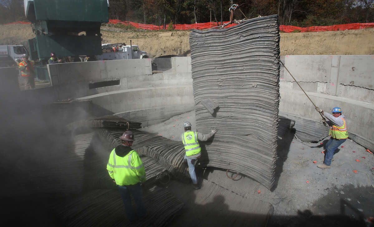 Fred Strechenwein, Gabe Phillips, and Bill Schwartz move blast mats on Thursday, Oct. 24, 2013, in Newburgh, N.Y. Contractors began blasting down 900 feet as DEP begins constructing a $1 billion bypass tunnel so it can shutdown and repair its Rondout-West Branch aqueduct tunnel. (AP Photo/Times Herald-Record, Jeff Goulding) ORG XMIT: NYMID105