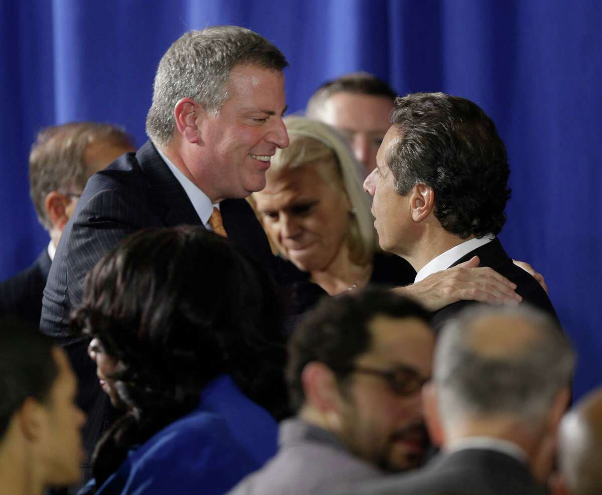 Mayoral candidate Bill de Blasio, left, talks with New York Governor Andrew Cuomo as they take their seats for a speech by President Barack Obama at Pathways in Technology Early College High School in Brooklyn, New York, Friday, Oct. 25, 2013. (AP Photo/Seth Wenig) ORG XMIT: NYSW120