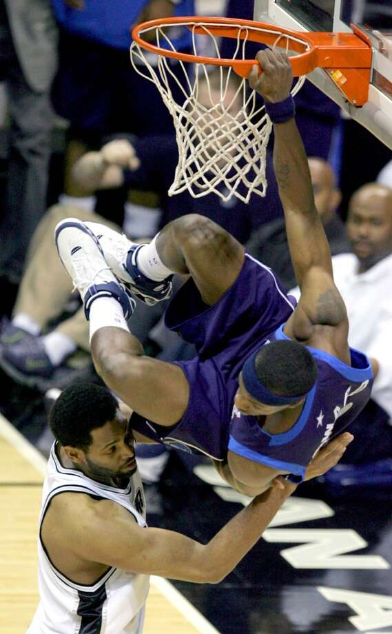The Mavericks' Josh Howard hangs from the rim and over the Spurs' Robert Horry on May 9, 2006, at the AT&T Center during Game 2 of the Western Conference Semifinals. Photo: Kevin Geil, San Antonio Express-News