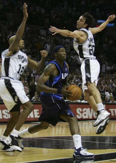 The Spurs' Bruce Bowen and Manu Ginobili defend the Mavericks' Josh Howard during Game 7 of the West