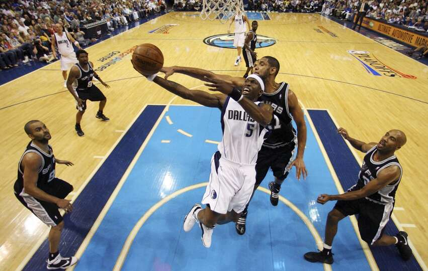 The Mavericks' Josh Howard drives to the basket between the Spurs' Tony Parker, Tim Duncan and Bruce