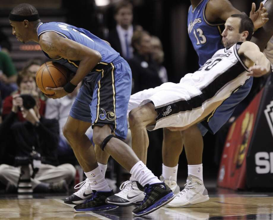 The Spurs' Manu Ginobili is knocked down by the Wizards' Josh Howard during the second half on Dec. 26, 2010, at the AT&T Center. Photo: Darren Abate, For The San Antonio Express-News