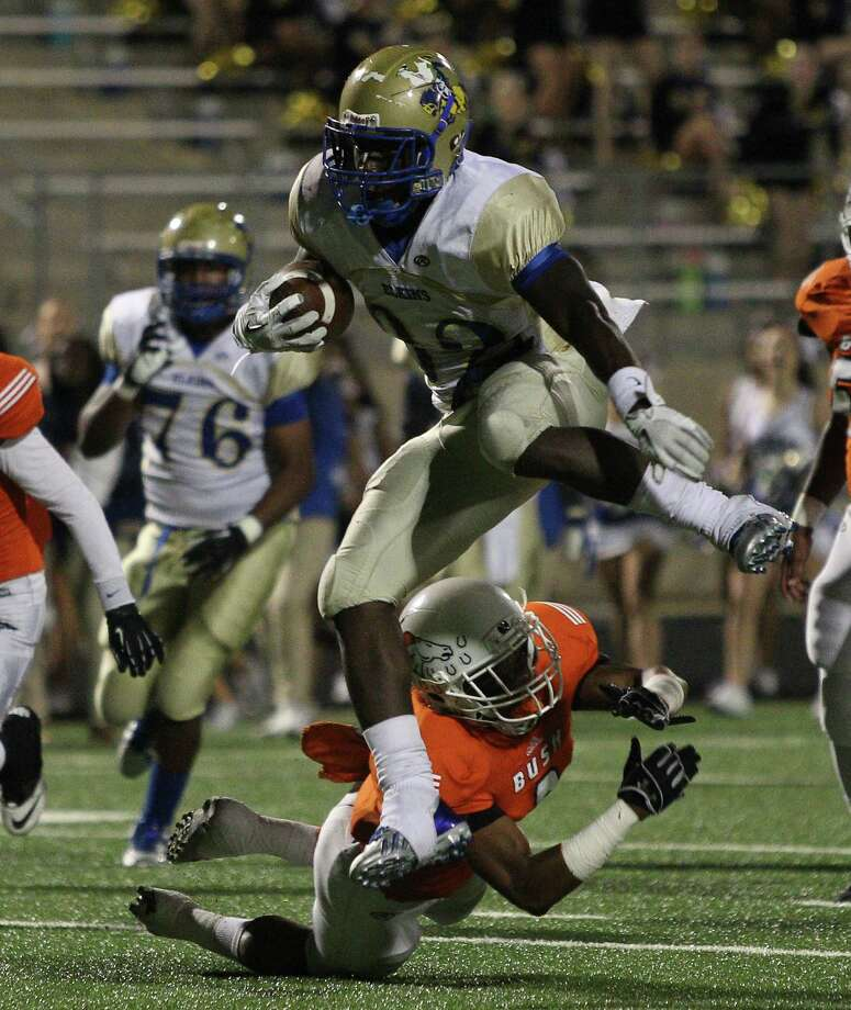 Fort Bend Elkins running back Timothy Jackson (32) leaps over Fort Bend Bush defensive back Darion Venible (8) for a touchdown in the first quarter during a high school football between Fort Bend Bush and Fort Bend Elkins Friday Oct. 25, 2013 in Missouri City, Texas. Photo: Bob Levey, Houston Chronicle / ©2013 Bob Levey