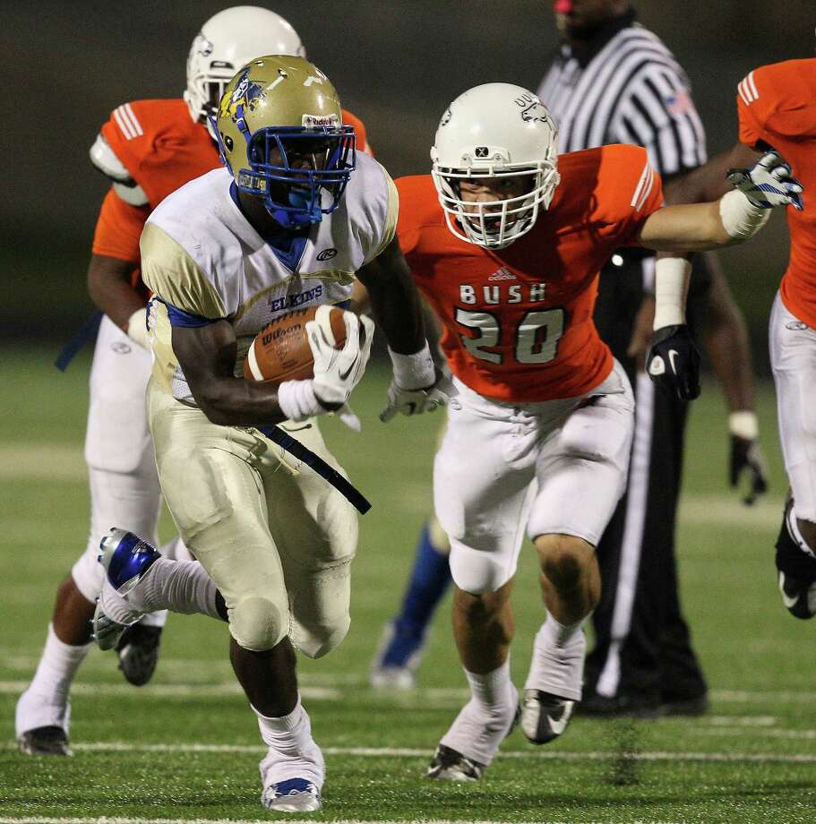 Fort Bend Elkins rb Timothy Jackson (32) rushes past Fort Bend Bush linebacker Adrian Covington (20)during a high school football between Fort Bend Bush and Fort Bend Elkins Friday Oct. 25, 2013 in Missouri City, Texas. Photo: Bob Levey, Houston Chronicle / ©2013 Bob Levey