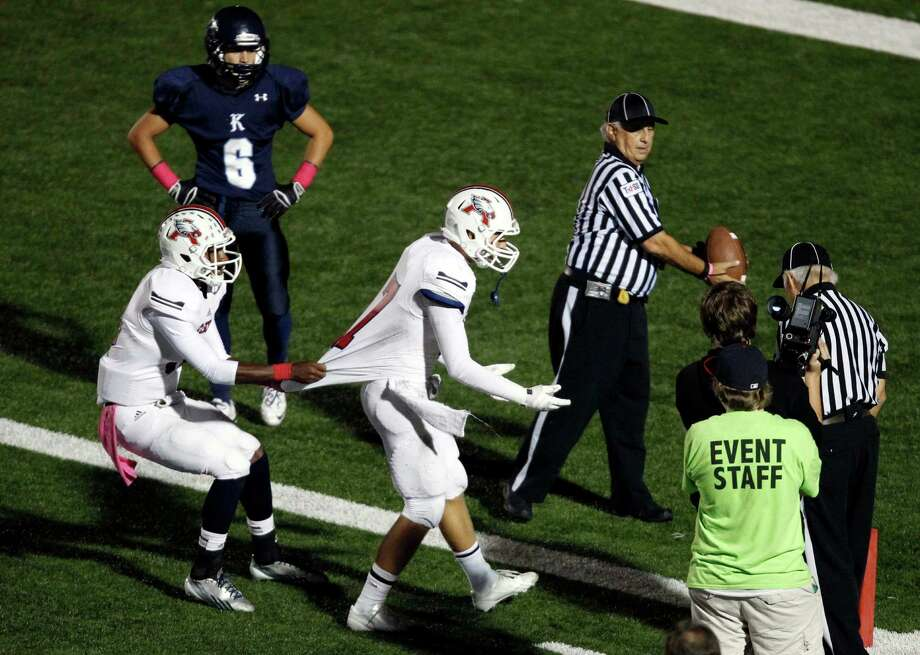 Atascocita's JJ Gibson (left) tries to pull teammate Taylor Stump back to the huddle as Stump argues with a referee during the second half of a high school football game, Friday, October 25, 2013 at Turner Stadium in Humble. Photo: Eric Christian Smith, For The Chronicle