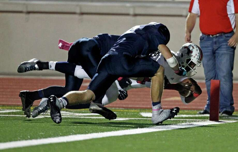 Atascocita's Greg Campbell, right, dives into the end zone for a touchdown past Kingwood's Cameron Nall during the first half of a high school football game, Friday, October 25, 2013 at Turner Stadium in Humble. Photo: Eric Christian Smith, For The Chronicle