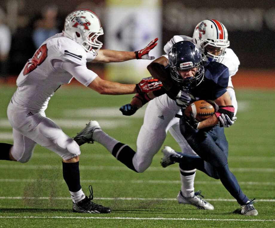 Kingwood's Griifin Lay is tackled by Atascocita's Ramsey Thunder and Matthew Montgomery, left, during the first half of a high school football game, Friday, October 25, 2013 at Turner Stadium in Humble. Photo: Eric Christian Smith, For The Chronicle
