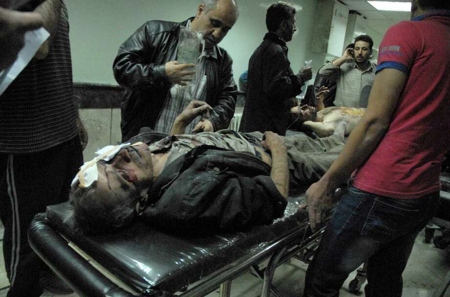 This picture released by the Syrian Arab News Agency shows wounded men treated at a hospital after a car bomb near the Osama Bin Zeid mosque near Damascus, Syria. Syrian troops killed at least 40 rebel fighters. Photo: AFP / Getty Images