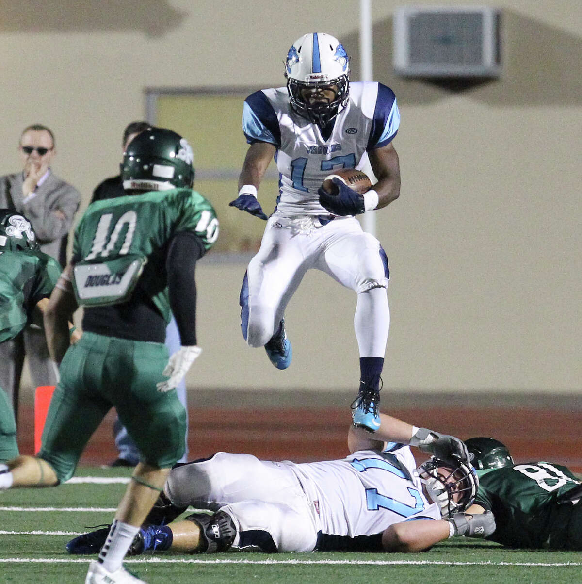 Johnson's Braedon Williams (17) leaps over players during the game against the Reagan Rattlers at Comalander Stadium on Friday, Oct. 25, 2013.