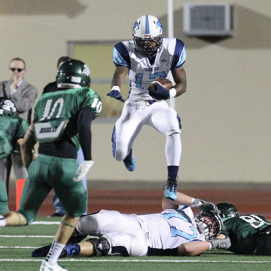 Johnson's Braedon Williams (17) leaps over players during the game against the Reagan Rattlers at Comalander Stadium on Friday, Oct. 25, 2013. Photo: Kin Man Hui, San Antonio Express-News / ©2013 San Antonio Express-News