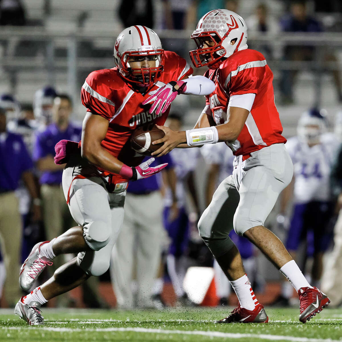 Judson's Malik Pryor (left) takes a hand off from Rayjohn Austin-Ramsey during the first quarter of their game at Rutledge Stadium on Friday, Oct. 25, 2013. Judson set a state record for consecutive winning seasons at 37 with the victory over the Rattlers. MARVIN PFEIFFER/ mpfeiffer@express-news.net
