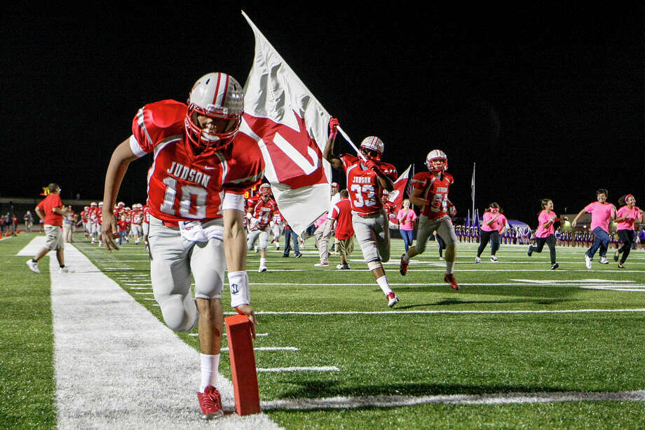 Judson's Rayjohn Austin-Ramsey (left) knocks down the pylon as the Rockets take a field, a long standing Rocket tradition, prior to the start of their game with San Marcos at Rutledge Stadium on Friday, Oct. 25, 2013.  Judson won the game 72-18 and  set a state record for consecutive winning seasons at 37 with the victory.  MARVIN PFEIFFER/ mpfeiffer@express-news.net Photo: Marvin Pfeiffer, San Antonio Express-News / Express-News 2013