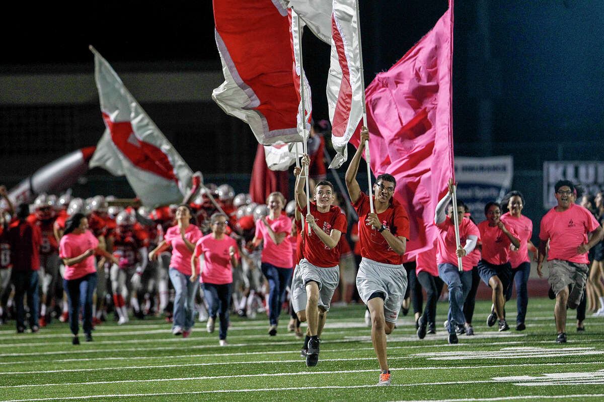 The Judson Rockets, led by members of the Judson Health Science Department clad in pink, take the field prior to their game with San Marcos at Rutledge Stadium on Friday, Oct. 25, 2013. MARVIN PFEIFFER/ mpfeiffer@express-news.net
