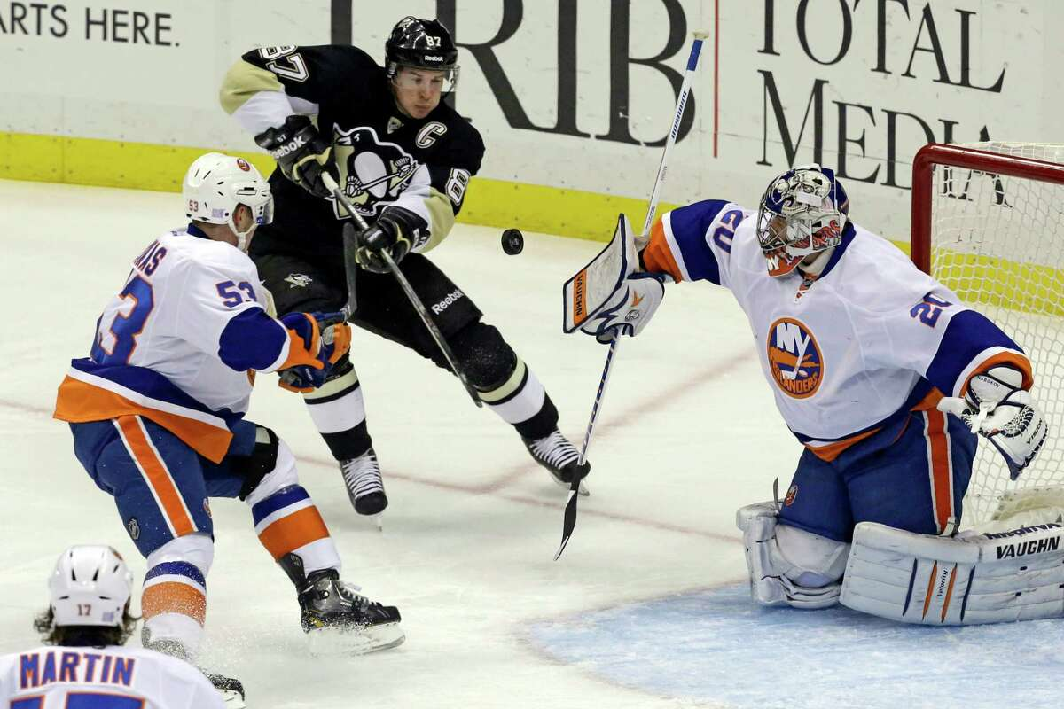 New York Islanders goalie Evgeni Nabokov (20) blocks a shot as Pittsburgh Penguins' Sidney Crosby, center, tries to bat the rebound in front of Casey Cizikas (53) during an NHL hockey game in Pittsburgh, Friday, Oct. 25, 2013. (AP Photo/Gene J. Puskar) ORG XMIT: PAGP105