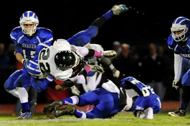 Shenendehowa's Jeremiah Smith, center, flies through the air when Shaker's defense tackles him during their Class AA quarterfinal football game against  on Friday, Oct. 25, 2013, at Shaker High in Latham, N.Y. (Cindy Schultz / Times Union) Photo: Cindy Schultz / 00024383A