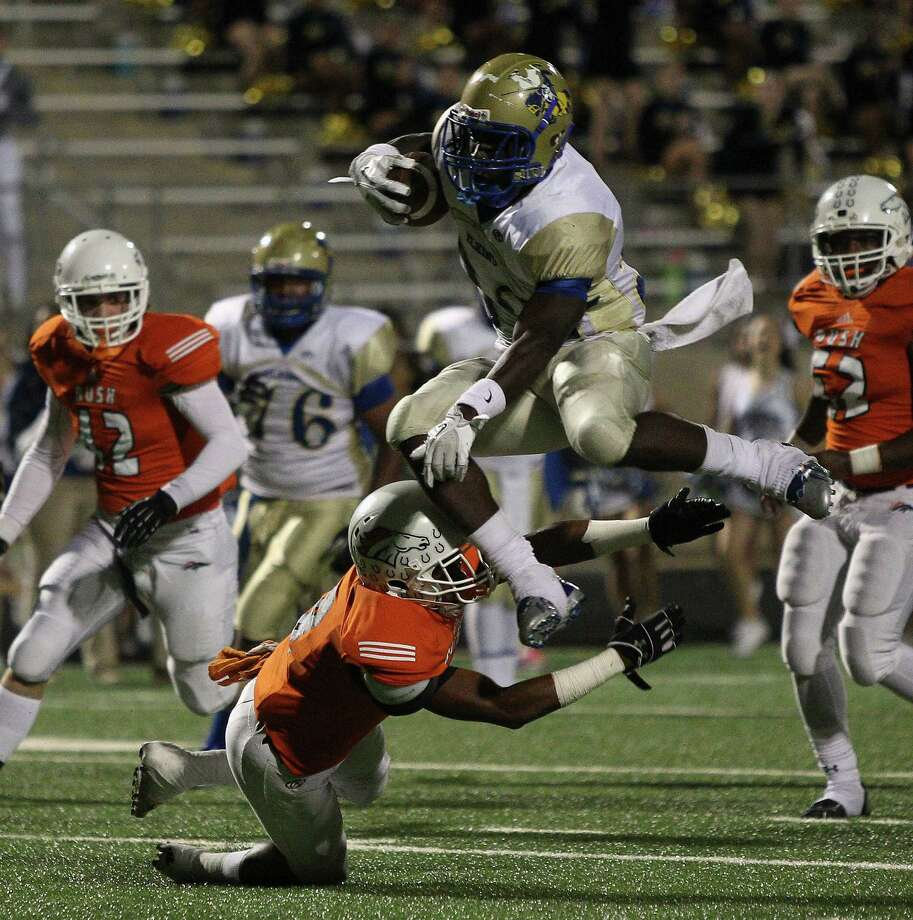 Elkins running back Timothy Jackson turns the Knights' ground game into an aerial attack as he leaps over Bush defensive back Darion Venible on his way to a first-quarter touchdown in the District 23-5A showdown. Photo: Bob Levey, Photographer / ©2013 Bob Levey