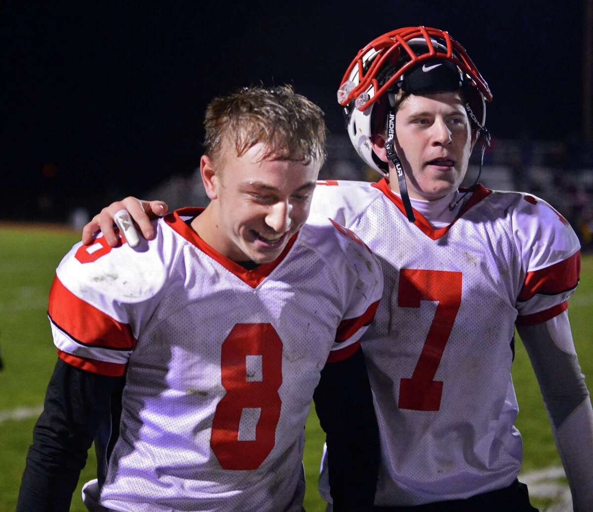 Guilderland's #8 Andrew Sentz, left, is congradulated by QB #7 Frank Gallo after Sentz kicked a final second field goal to win their Class AA quarterfinal football game against Colonie Friday Oct. 24, 2013, in Colonie, NY. (John Carl D'Annibale / Times Union)